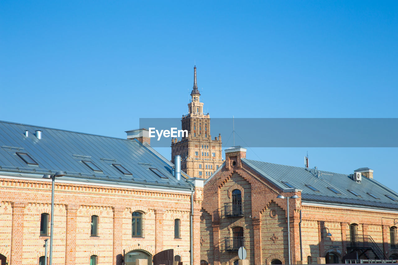 building exterior, architecture, built structure, sky, building, blue, place of worship, clear sky, religion, copy space, belief, spirituality, nature, low angle view, tower, sunlight, day, city, no people, spire, clock