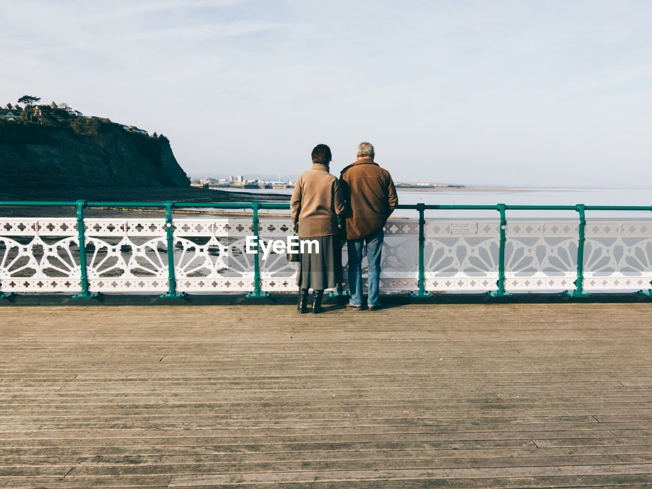Rear view of people standing on pier by beach against sky