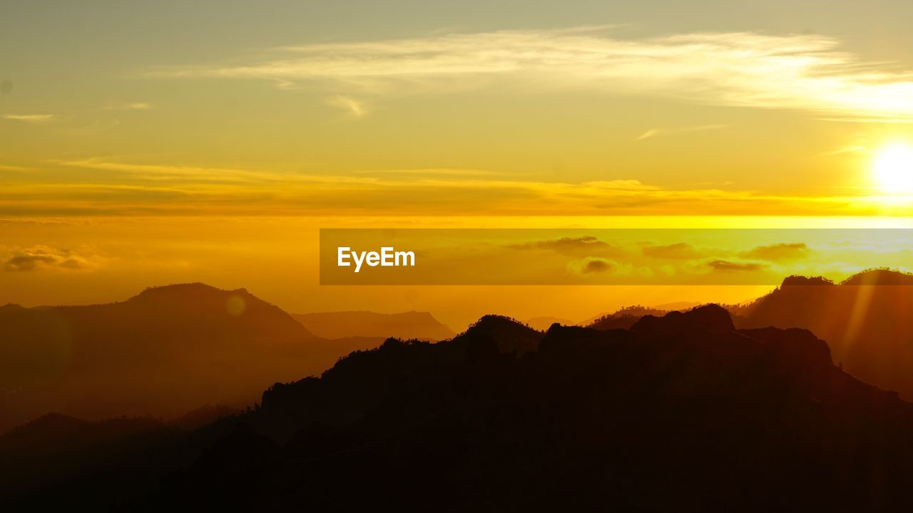 sunset, beauty in nature, scenics, nature, mountain, orange color, tranquil scene, silhouette, tranquility, sky, no people, idyllic, mountain range, yellow, outdoors, day
