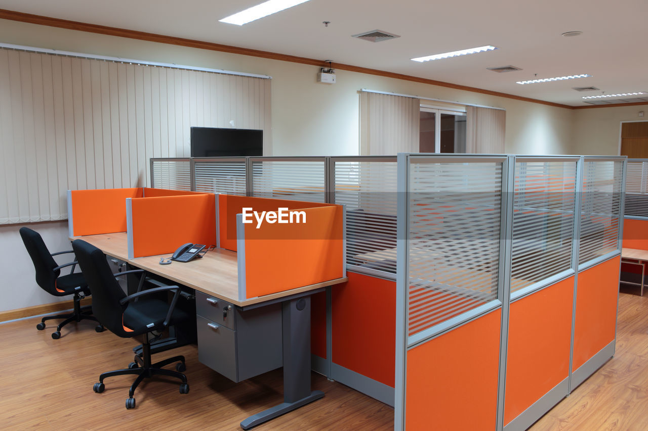indoors, furniture, seat, table, business, flooring, office, chair, absence, no people, orange color, empty, technology, ceiling, corporate business, wood, desk, architecture, illuminated