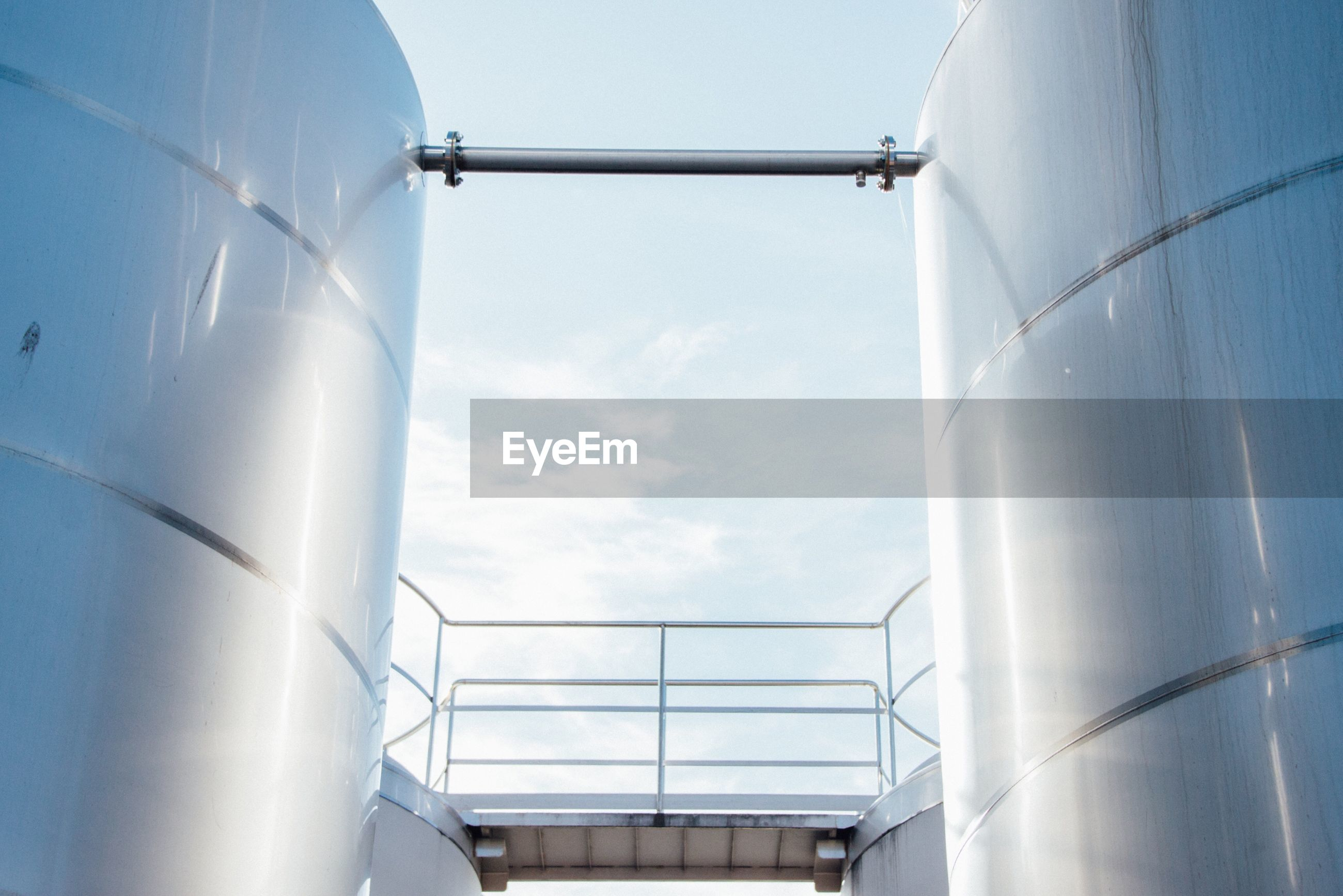 Low angle view of storage tanks against sky at factory