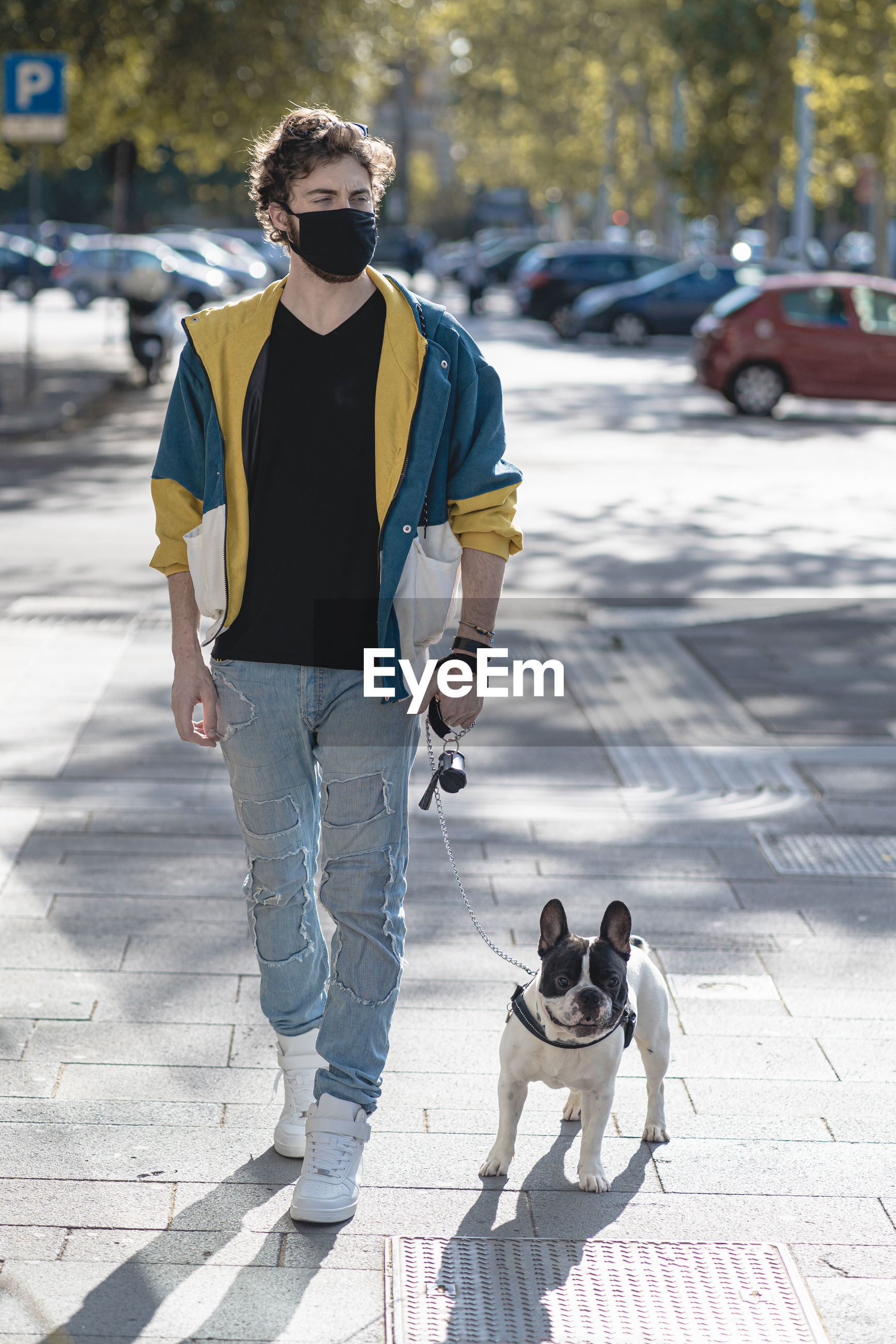 Man wearing mask walking with dog on street in city