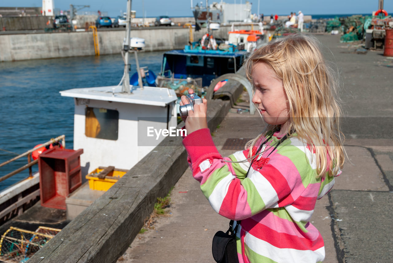 Side view of girl photographing with camera while standing at harbor