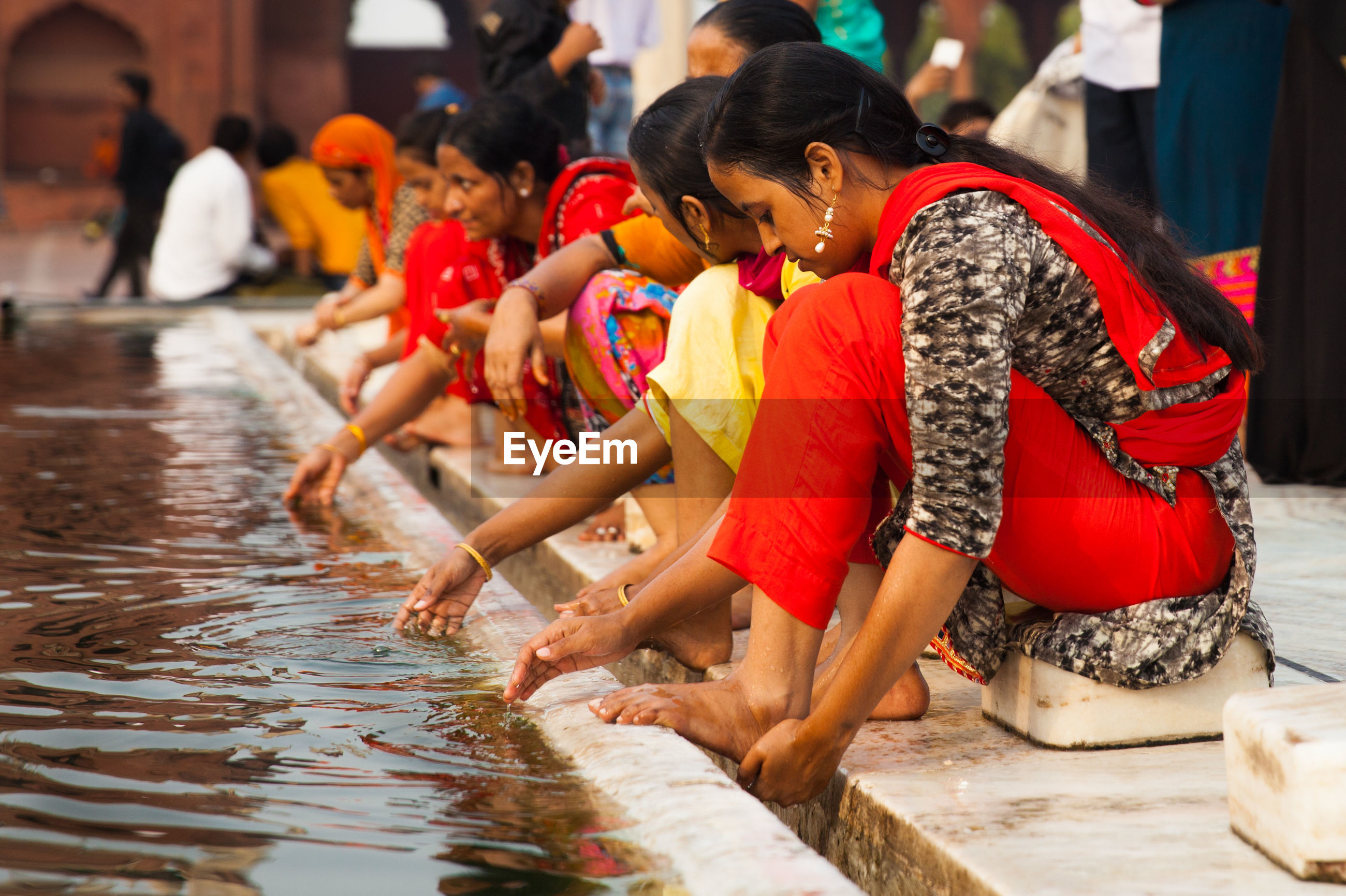 REAR VIEW OF PEOPLE SITTING IN WATER AT MARKET