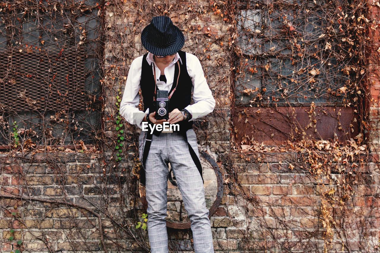 Retro-styled man with vintage medium format photo camera outdoors.