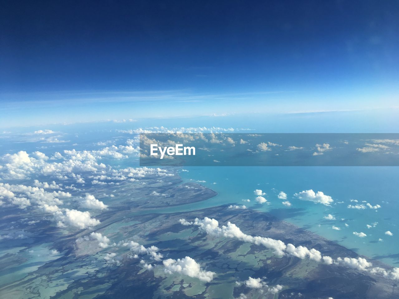 Aerial View Of Sea And Landscape Against Blue Sky