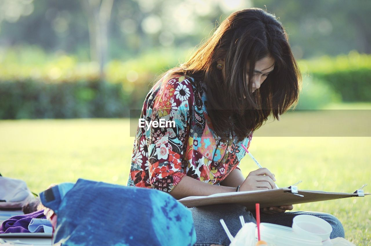 Young Woman Drawing While Sitting At Park