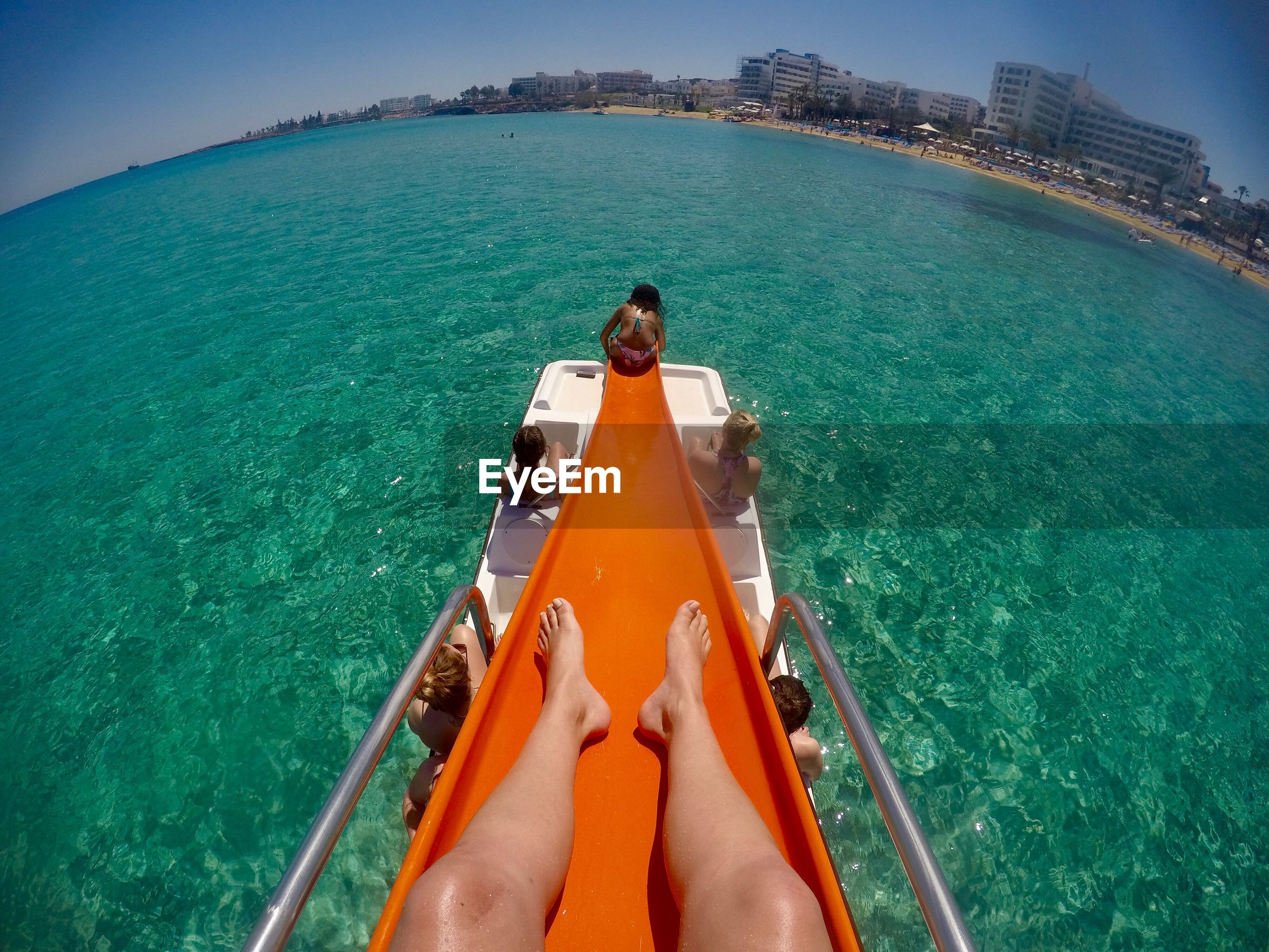 Low section of woman on slide in sea during sunny day
