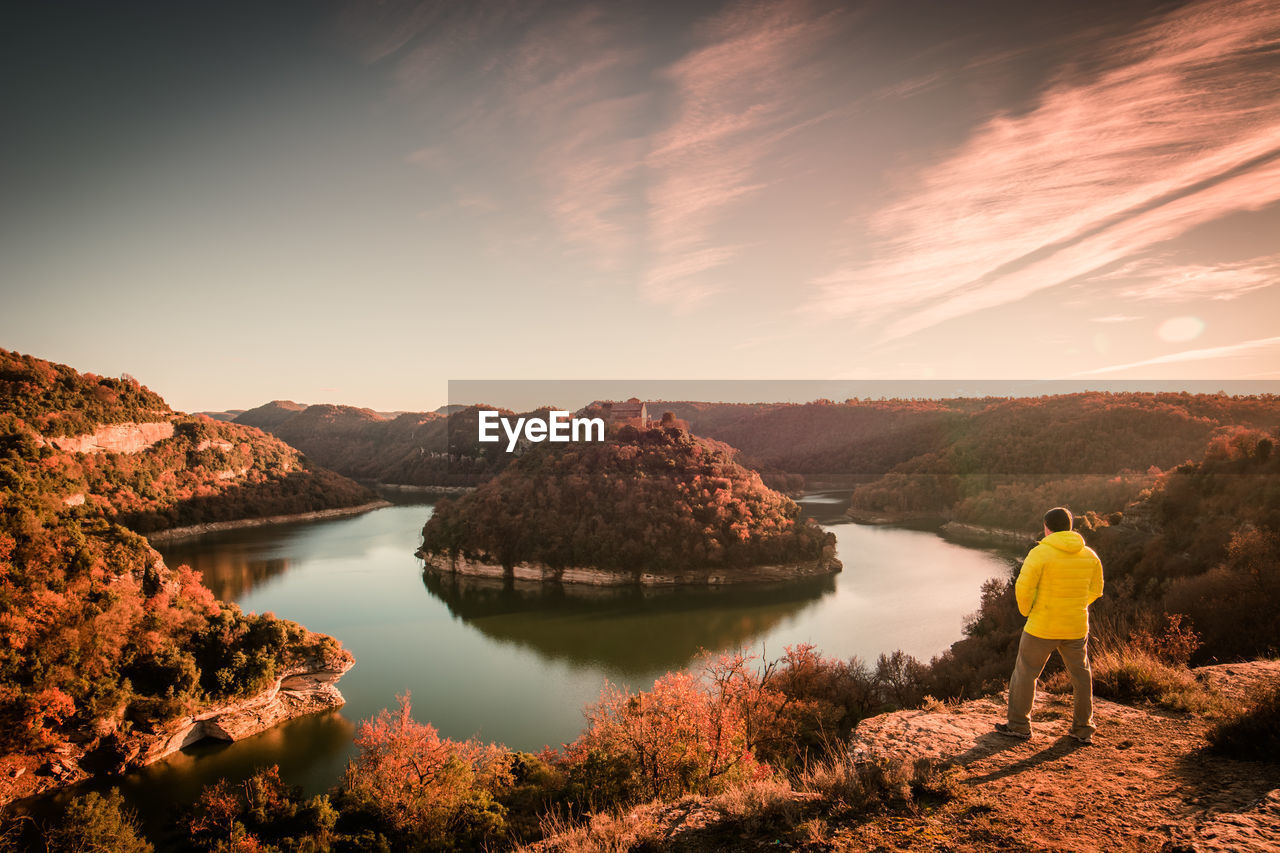 View of man standing by horseshoe bend in ter river and mountain with sant pere de casserres abbey
