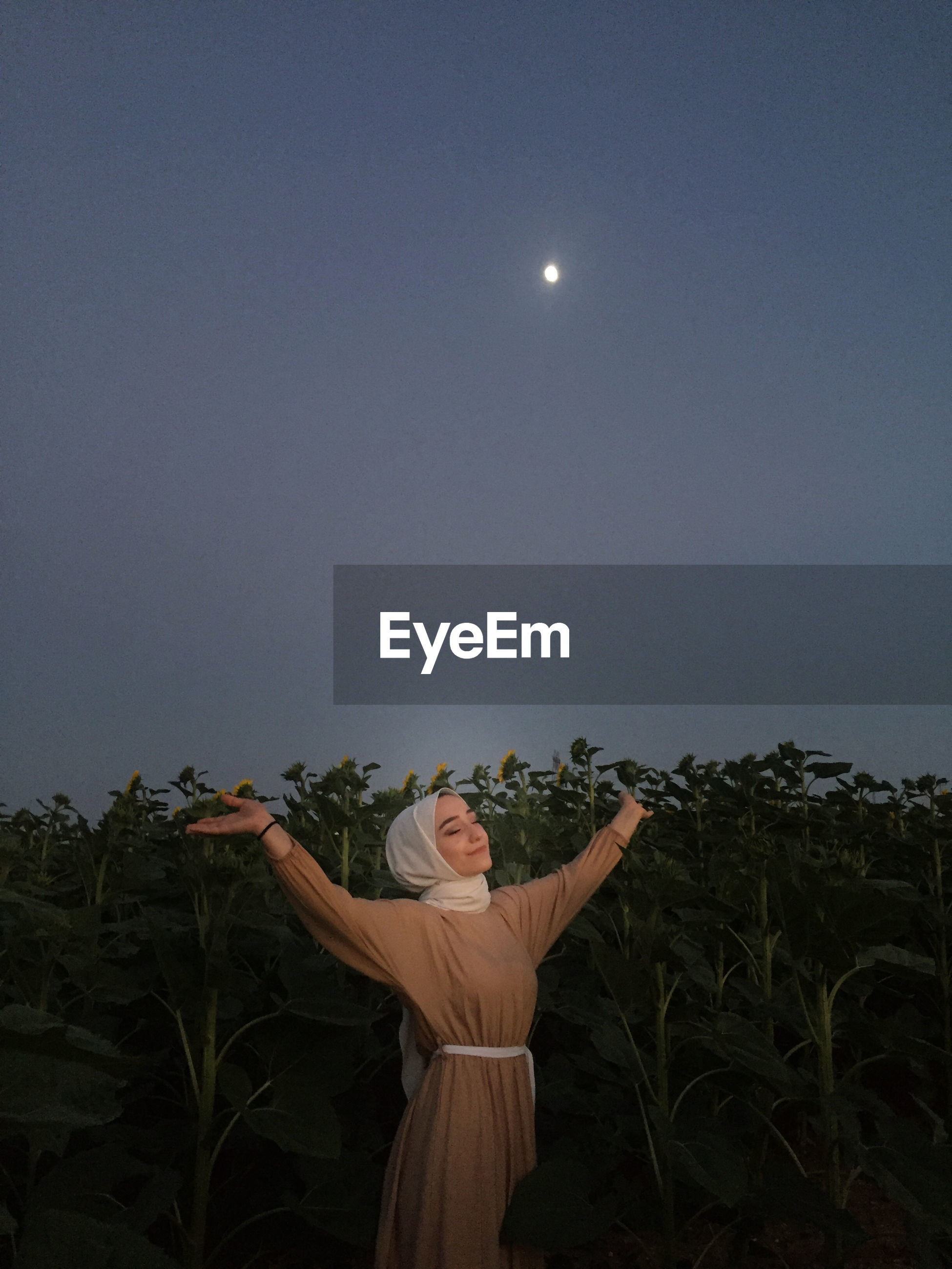 Smiling woman with arms outstretched standing in farm at night