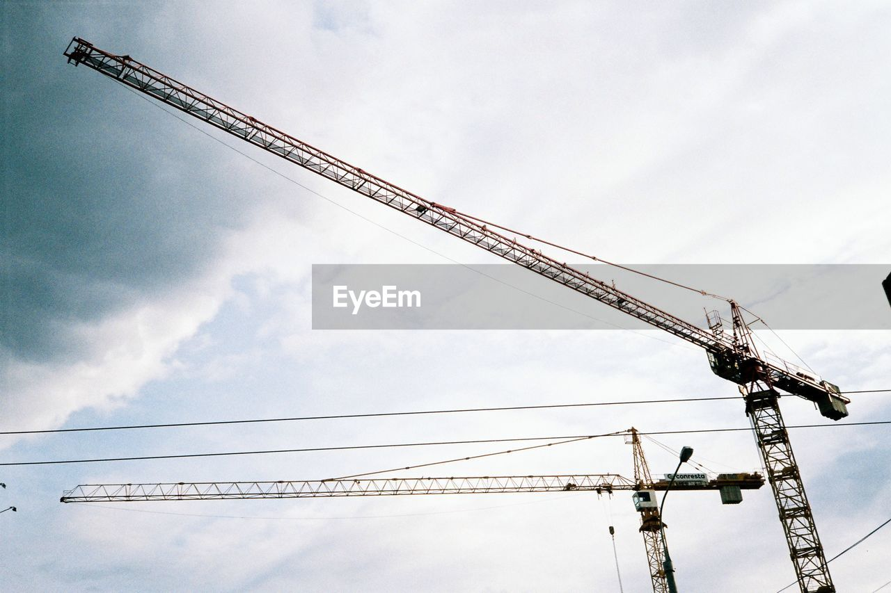 low angle view, sky, crane - construction machinery, no people, development, day, cloud - sky, outdoors, crane, industry