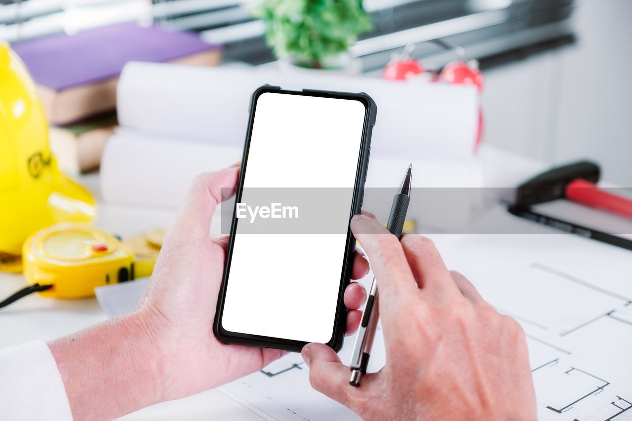 human hand, portable information device, wireless technology, one person, table, holding, smart phone, hand, technology, communication, human body part, mobile phone, screen, real people, connection, focus on foreground, telephone, touch screen, close-up, device screen, blank, finger