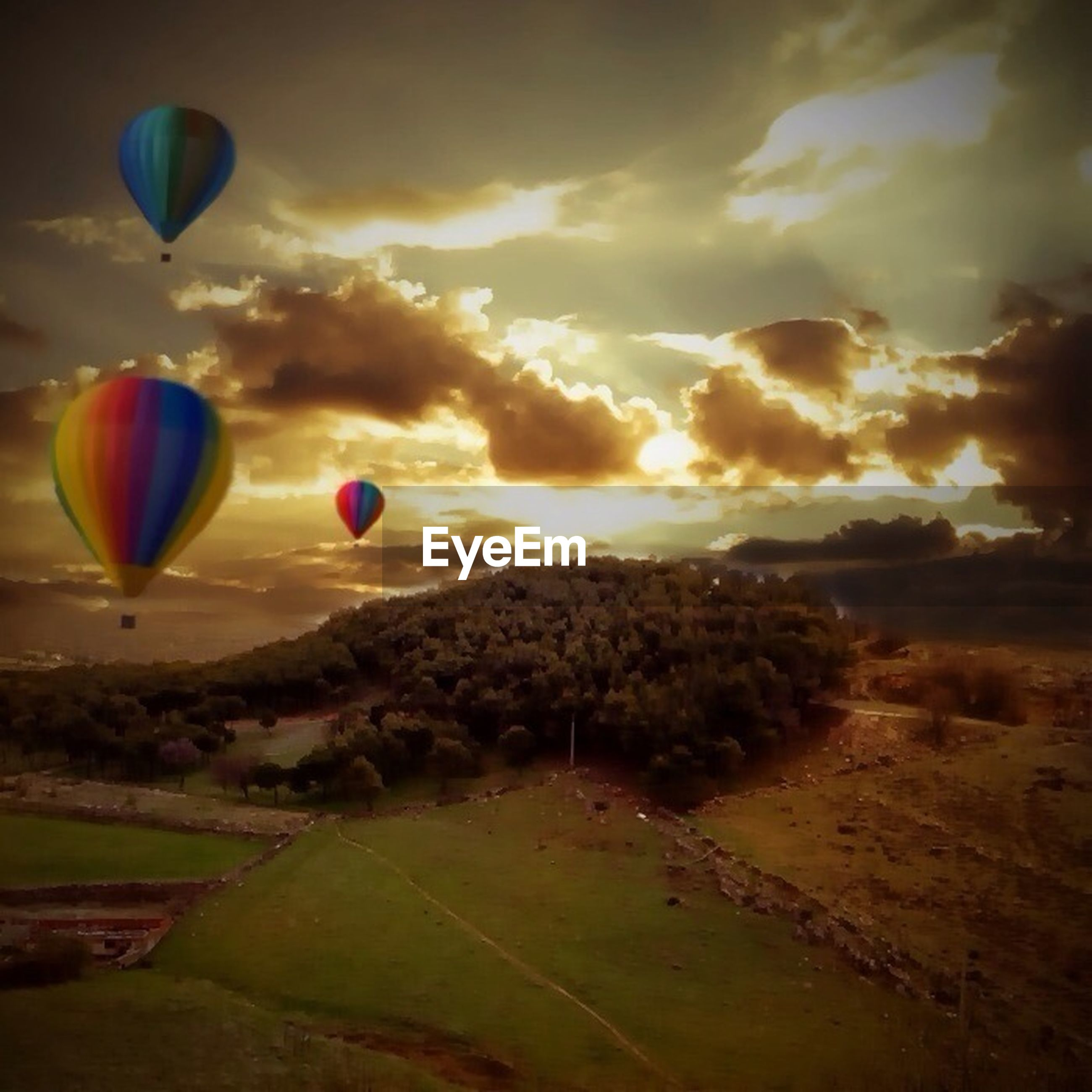 hot air balloon, mid-air, flying, parachute, sky, multi colored, landscape, scenics, beauty in nature, tranquil scene, tranquility, cloud - sky, nature, field, adventure, balloon, grass, paragliding, idyllic, outdoors