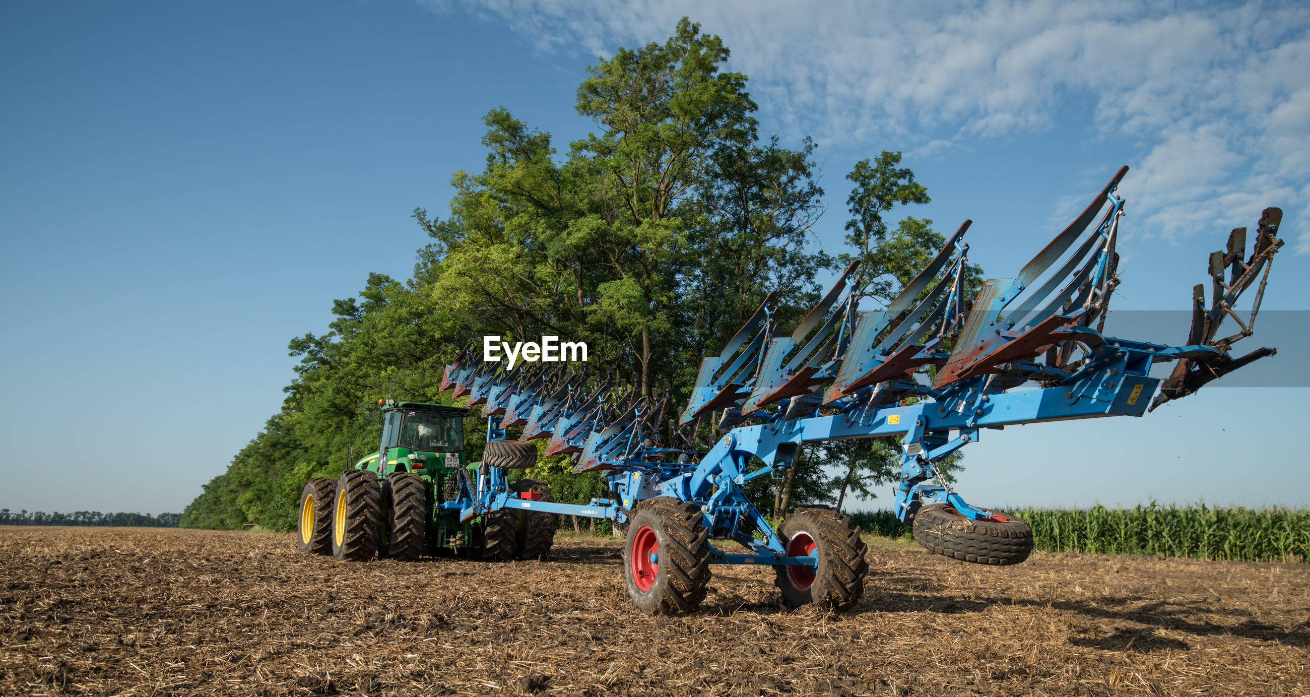 Low angle view of machinery and tractor on field against sky
