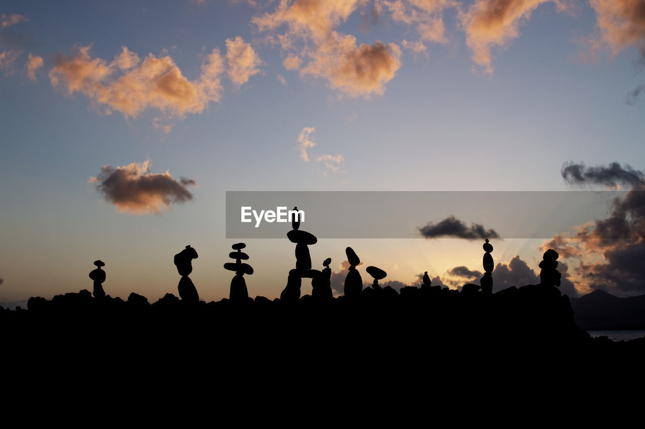 Stack of rocks against sky during sunset