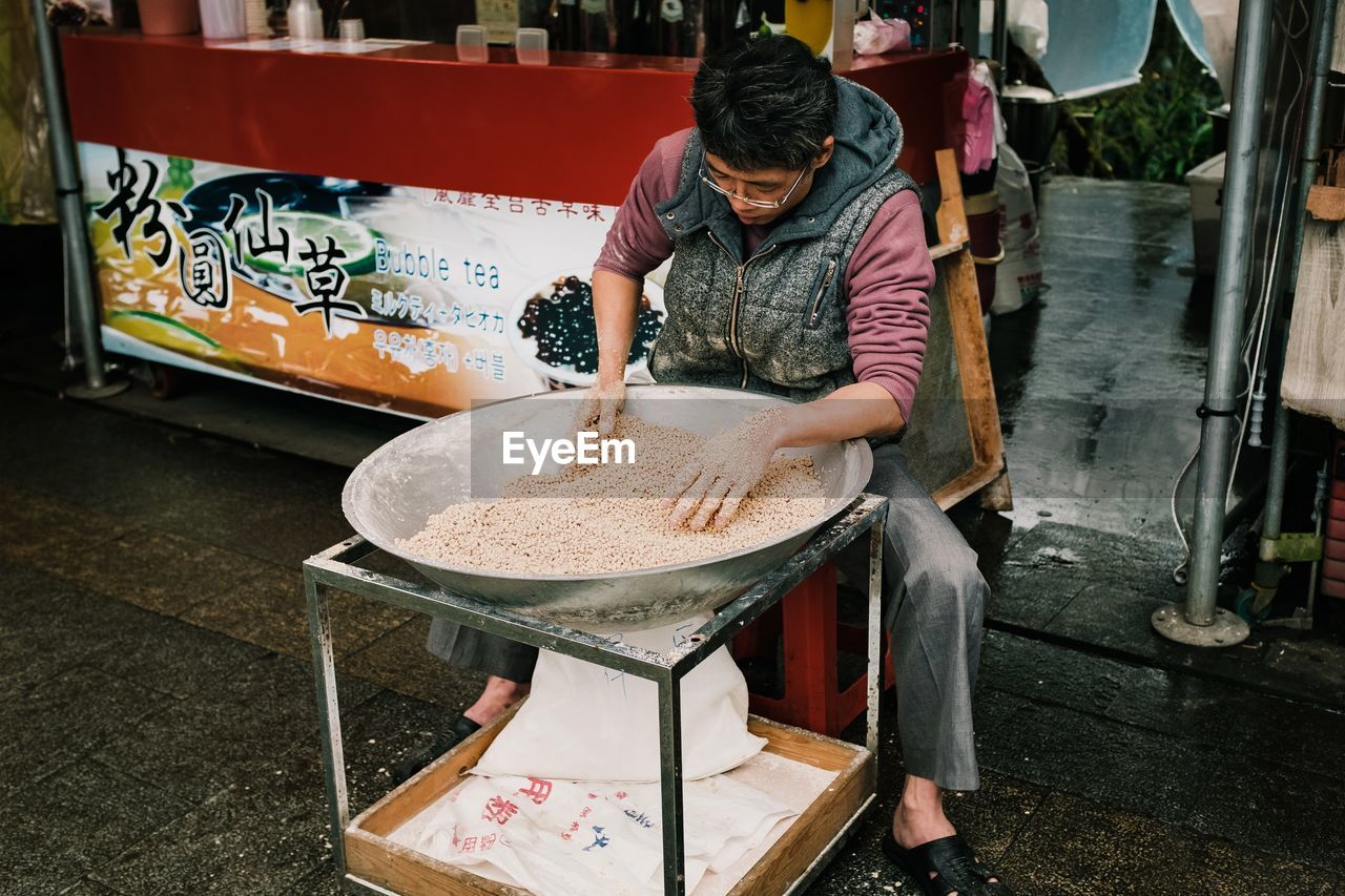 MIDSECTION OF MAN WORKING AT MARKET