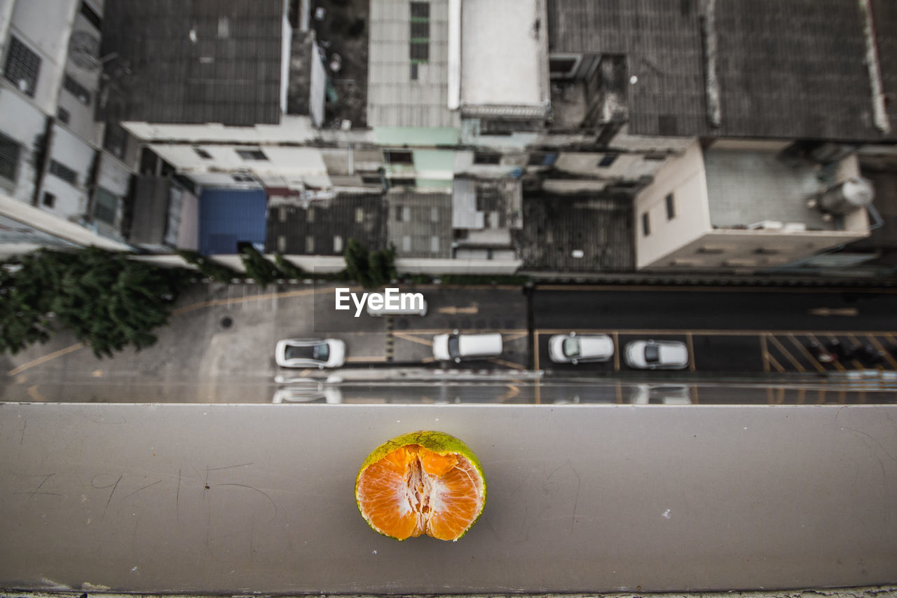 HIGH ANGLE VIEW OF ORANGE FRUIT ON BUILDING