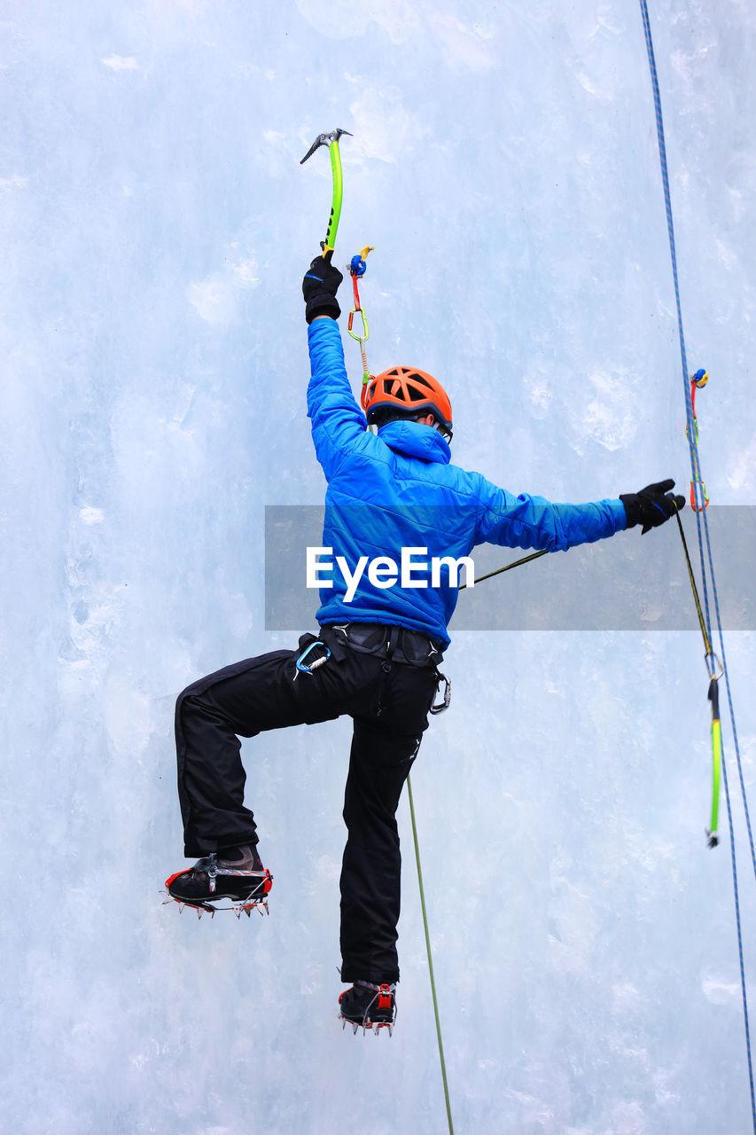 Rear view of man ice climbing