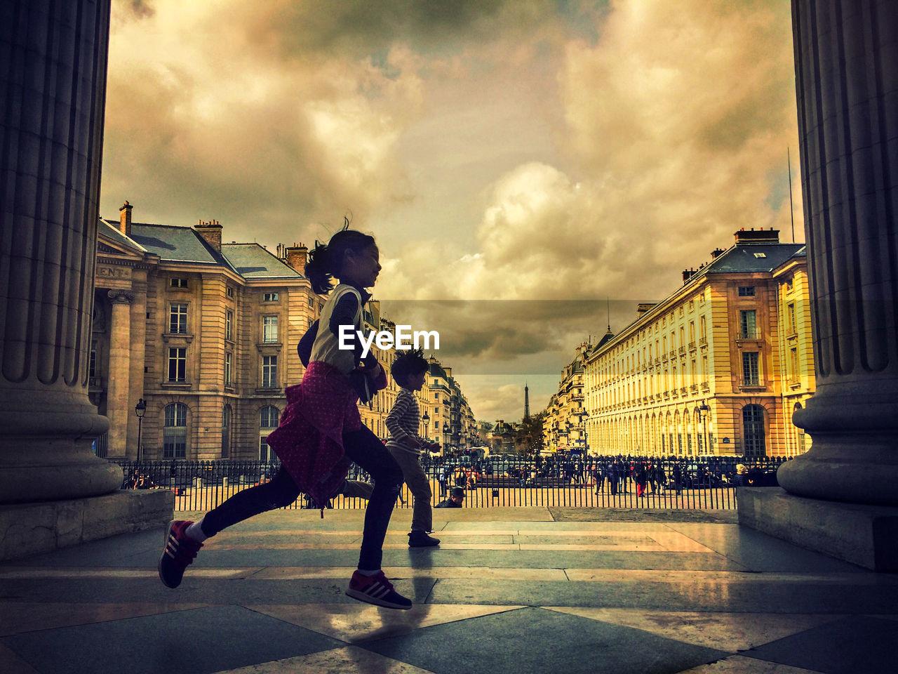 MAN WALKING IN CITY AGAINST SKY