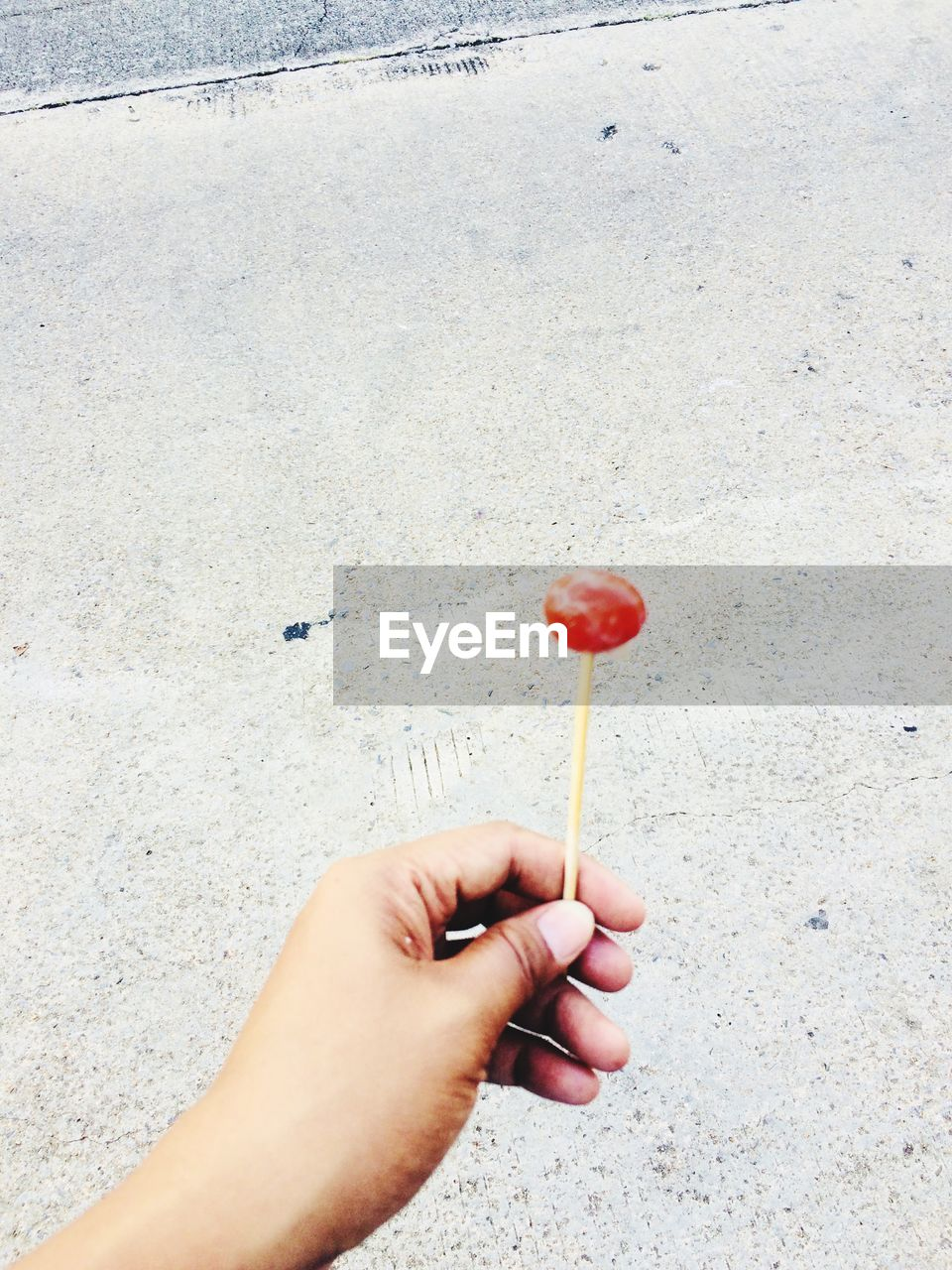 hand, human hand, human body part, one person, holding, lollipop, real people, food, food and drink, candy, sweet, day, unrecognizable person, sweet food, human finger, red, personal perspective, finger, indulgence, outdoors, temptation