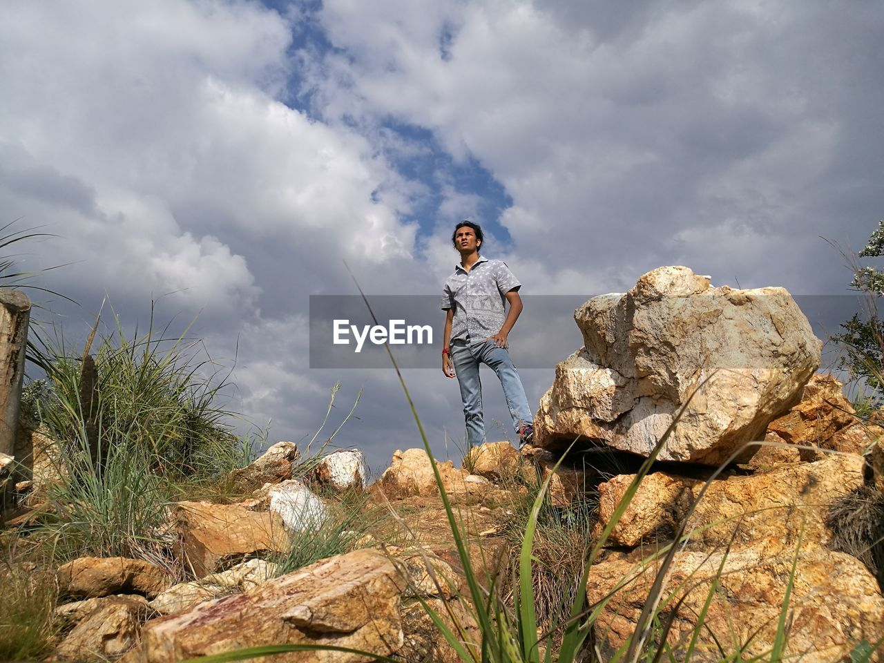 Low Angle View Of Man Standing On Rock Against Cloudy Sky