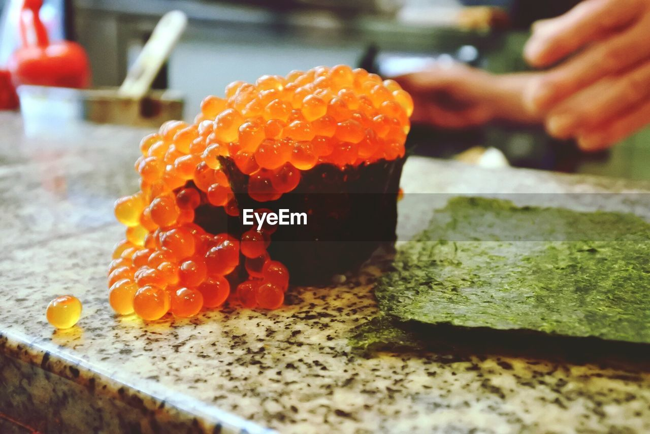 food, food and drink, freshness, indoors, close-up, selective focus, ready-to-eat, healthy eating, human hand, hand, fruit, wellbeing, still life, japanese food, table, serving size, rice, indulgence, sushi, sweet food, caviar, temptation