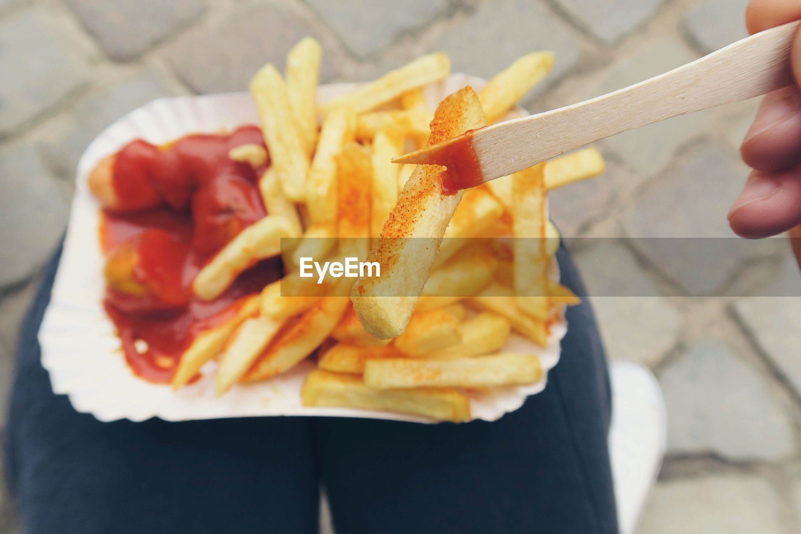 Close-up of person eating currywurst