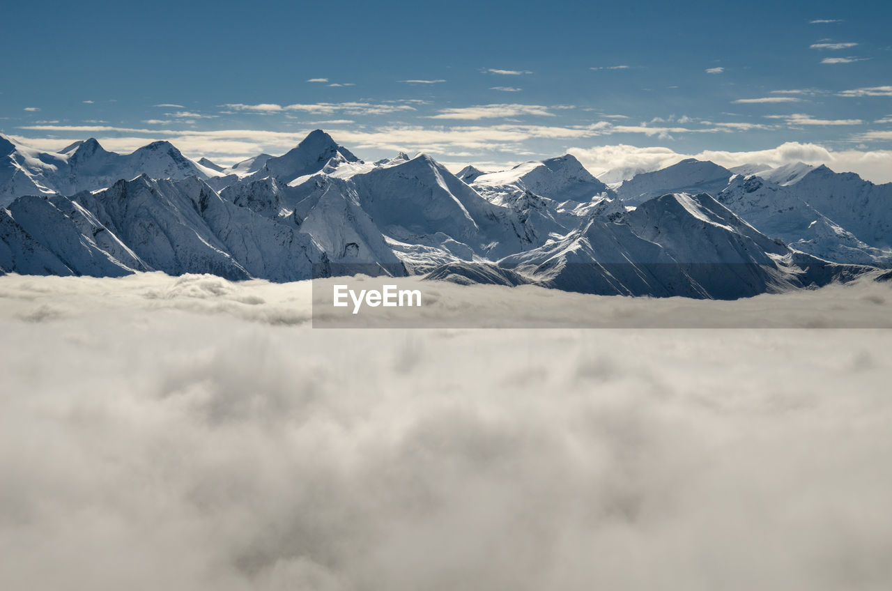 Scenic View Of Cloudscape By Snow Covered Mountains Against Sky