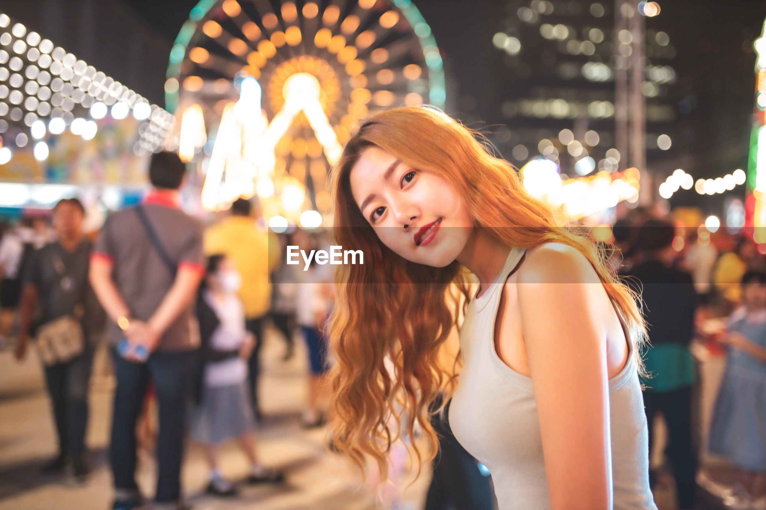 Portrait of young woman standing against illuminated ferris wheel at night