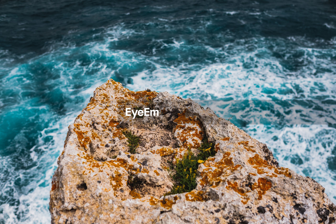 sea, water, solid, rock - object, rock, no people, nature, motion, wave, aquatic sport, high angle view, day, rough, rock formation, outdoors, beauty in nature, textured, sport, turquoise colored, power in nature, stack rock, rocky coastline