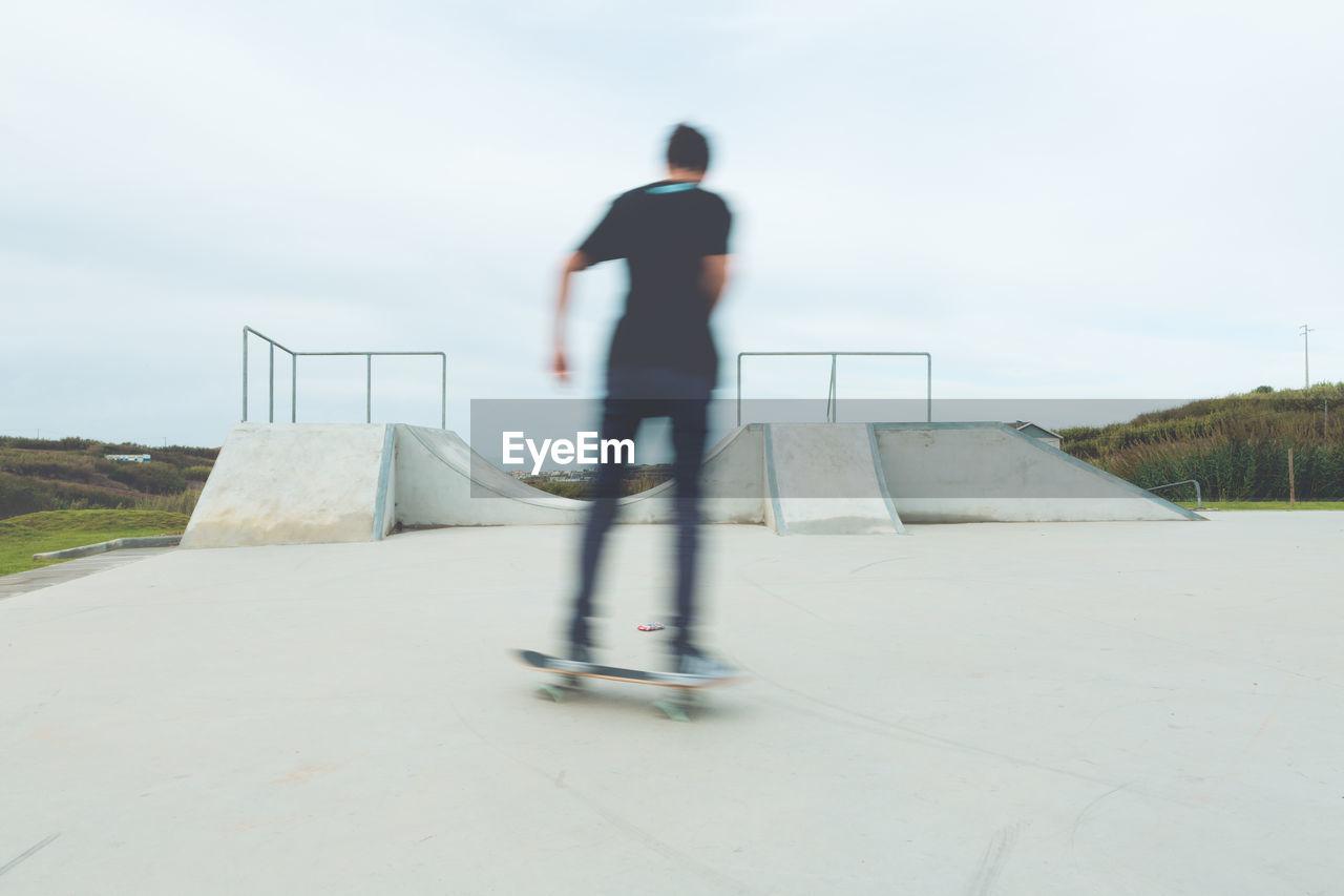 Blurred Image Of Man Skateboarding At Park