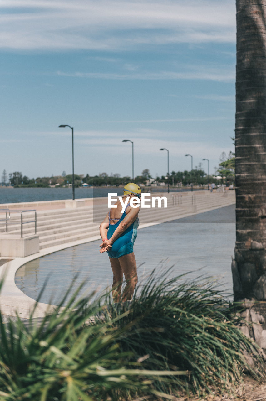 one person, plant, nature, sky, real people, water, architecture, full length, leisure activity, lifestyles, day, casual clothing, standing, built structure, building exterior, outdoors, city, sport, shorts