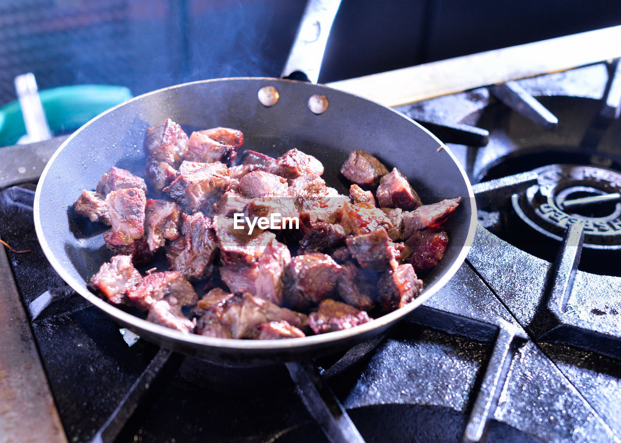 food, meat, preparation, food and drink, kitchen utensil, household equipment, stove, heat - temperature, freshness, pan, preparing food, appliance, kitchen, frying pan, cooking pan, close-up, no people, healthy eating, indoors, wellbeing, beef, skillet- cooking pan