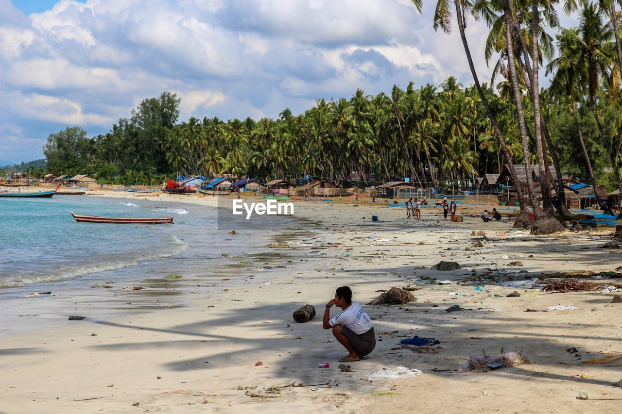 tree, water, real people, land, beach, plant, sky, sand, cloud - sky, nature, men, day, lifestyles, leisure activity, sea, incidental people, nautical vessel, people, palm tree, outdoors