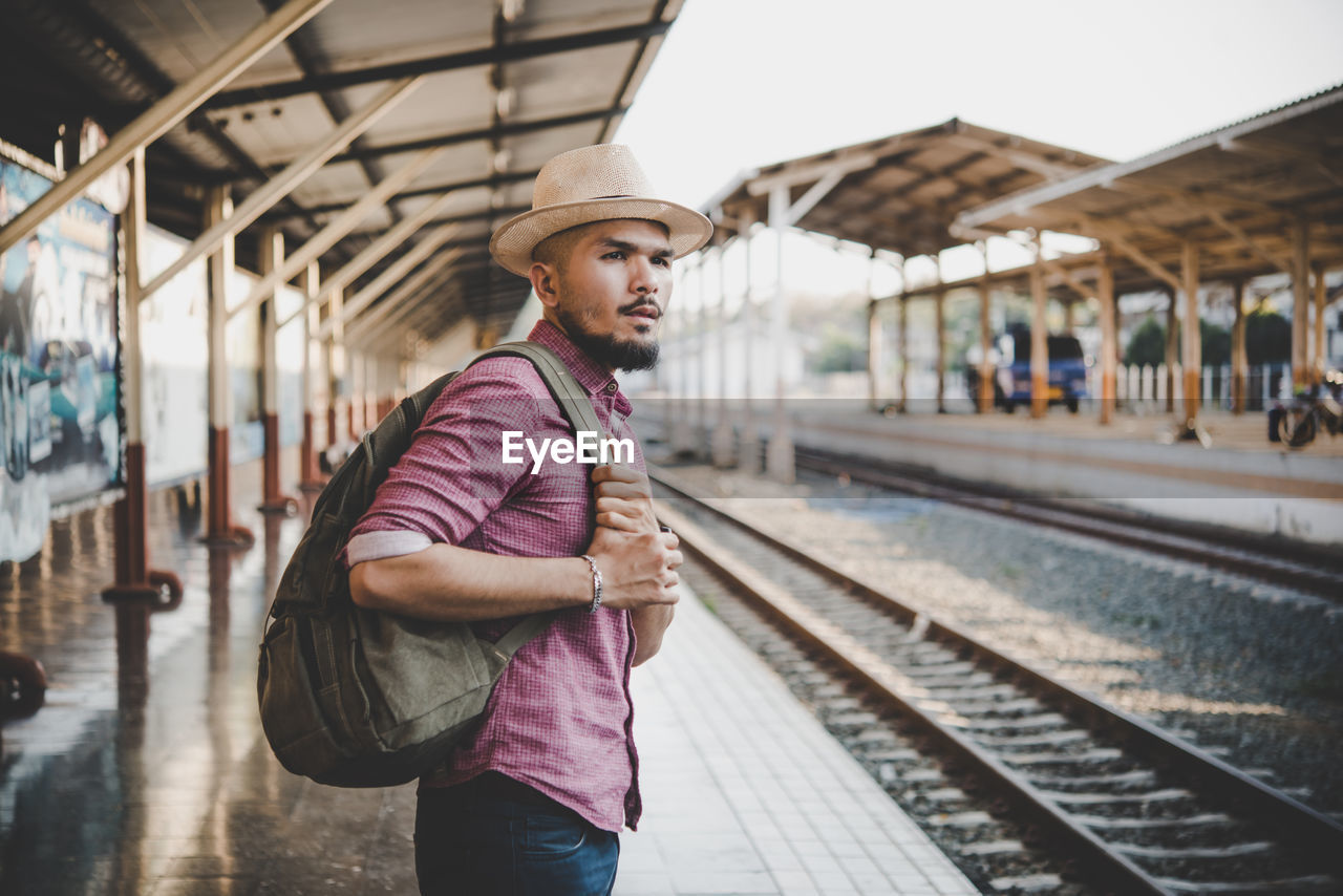 Side View Of Man With Backpack Standing At Railroad Station