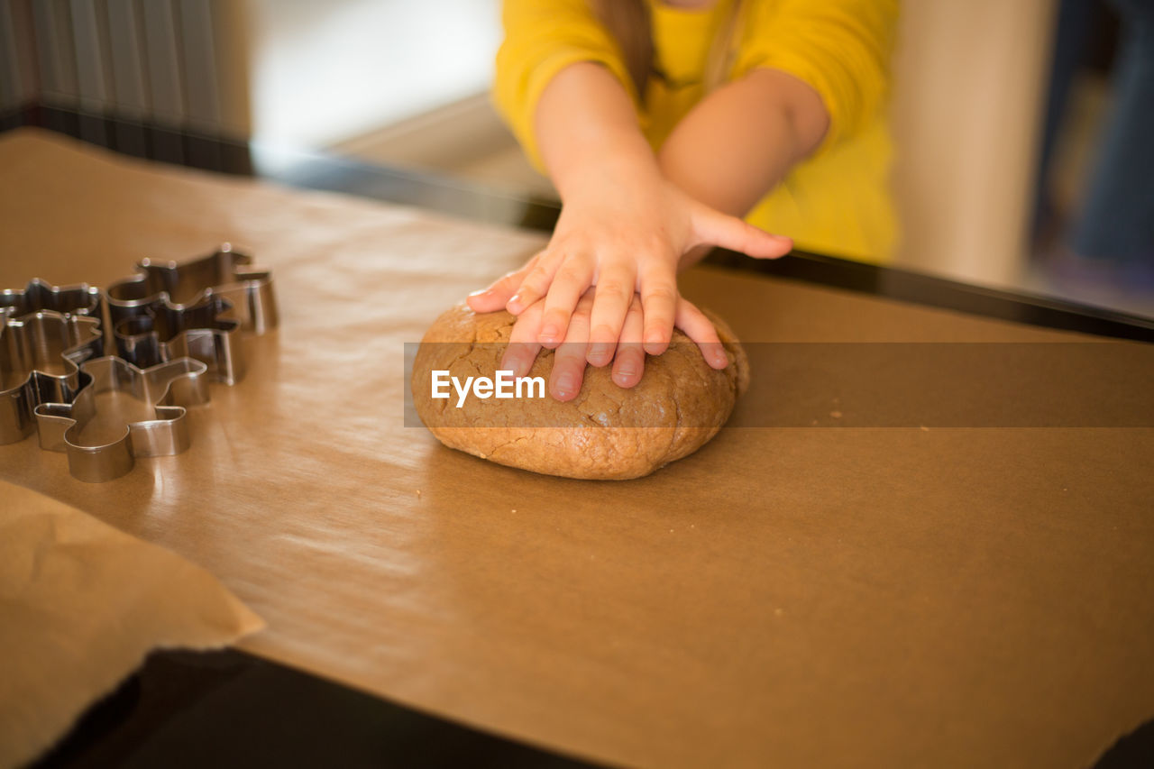 Midsection Of Woman Holding Dough On Kitchen Counter