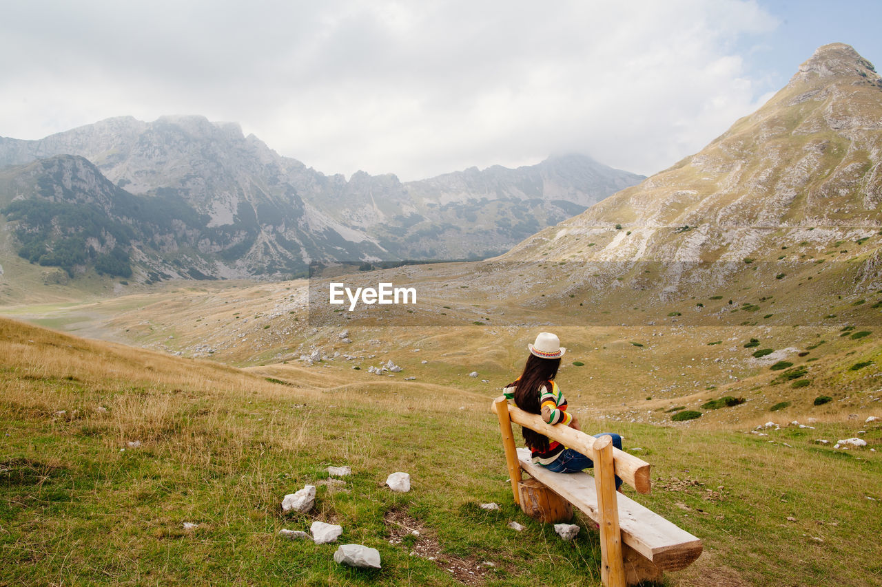 Woman Sitting On Bench Against Mountains