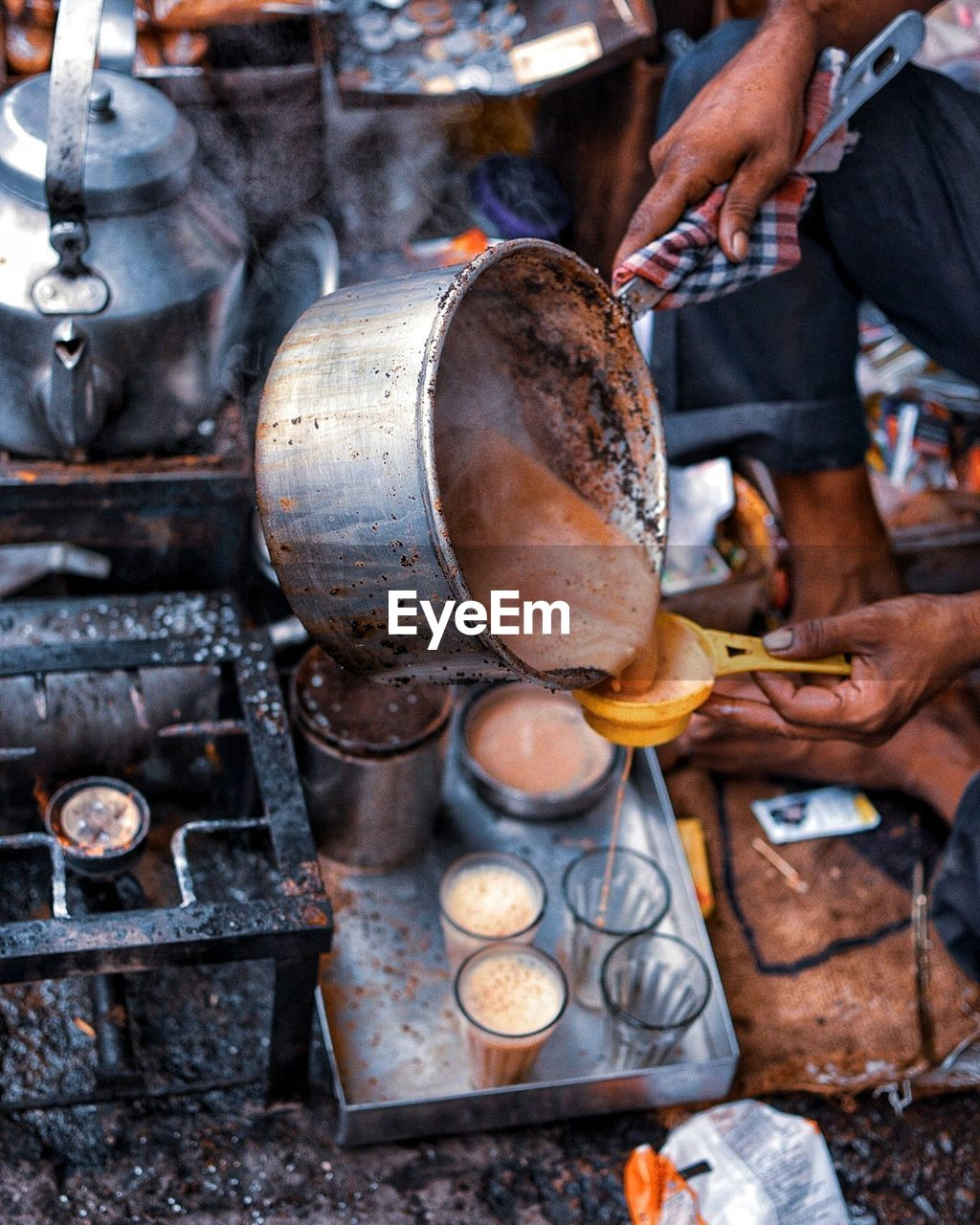 human hand, hand, human body part, one person, occupation, day, real people, holding, men, metal, working, heat - temperature, food and drink, focus on foreground, food, business, preparation, kitchen utensil, outdoors