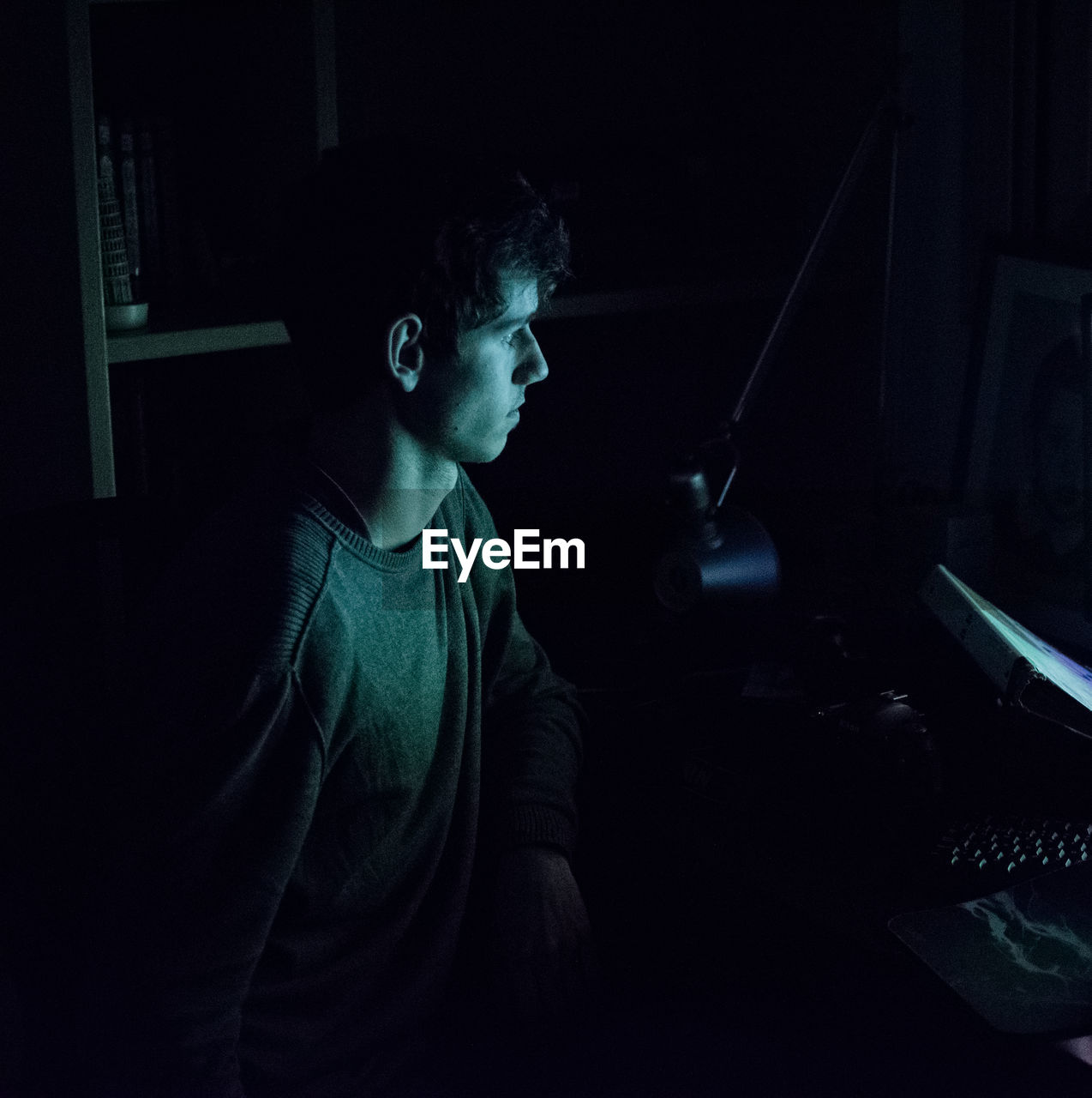 Young Man Looking Into Computer In Room At Home