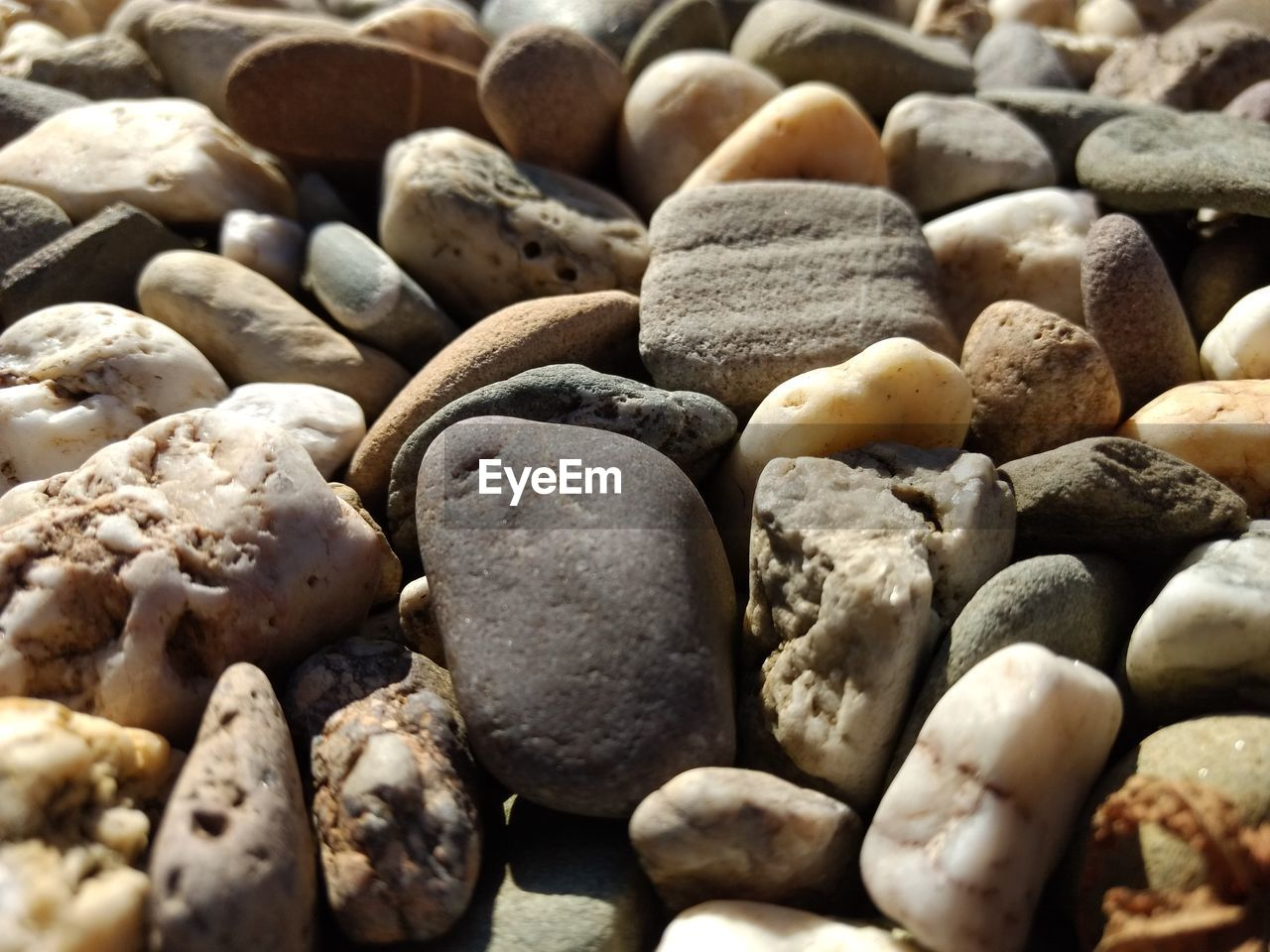 FULL FRAME SHOT OF PEBBLES ON STONES