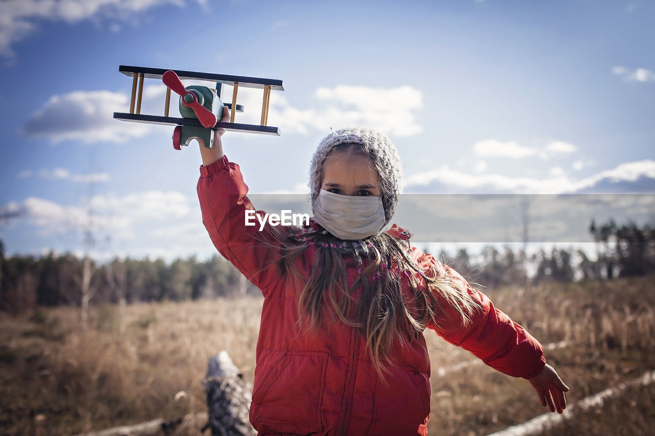 Girl wearing respirator masks staying in forest with toy air plane, guideline in quarantine time