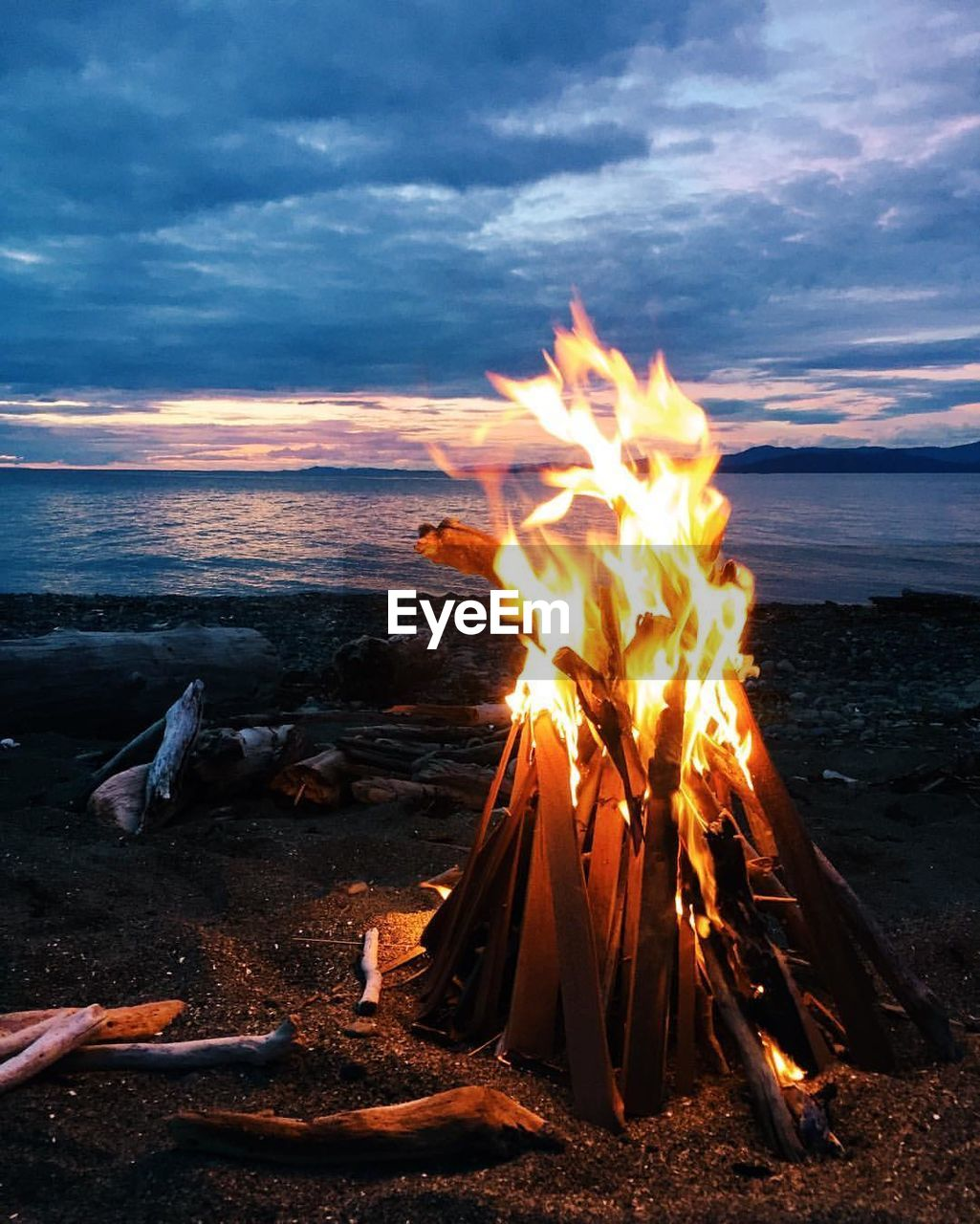 Bonfire By Sea Against Cloudy Sky At Dusk