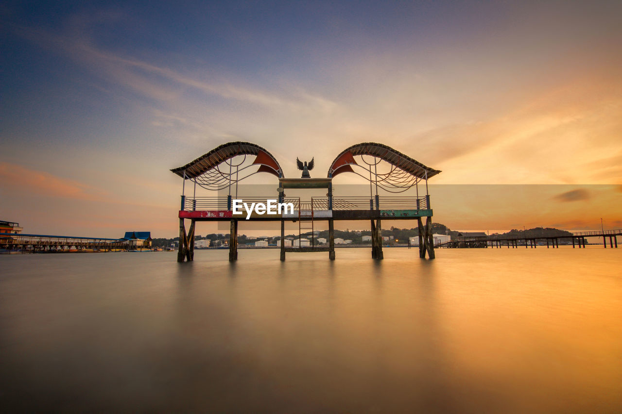 sky, sunset, water, architecture, cloud - sky, built structure, nature, waterfront, scenics - nature, beauty in nature, orange color, reflection, outdoors, no people, transportation, bridge, sea, travel destinations, bridge - man made structure