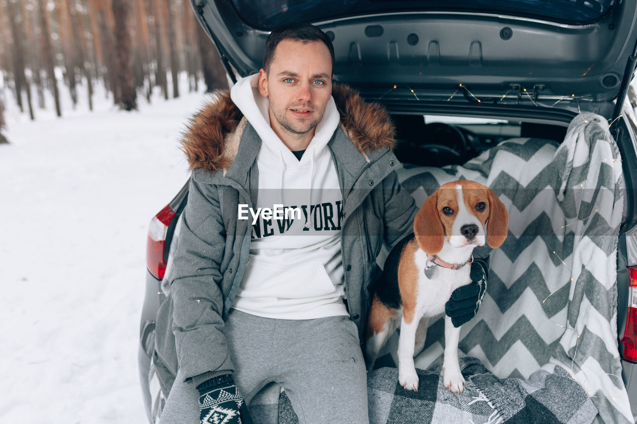 Portrait of man with dog sitting in car trunk during forest