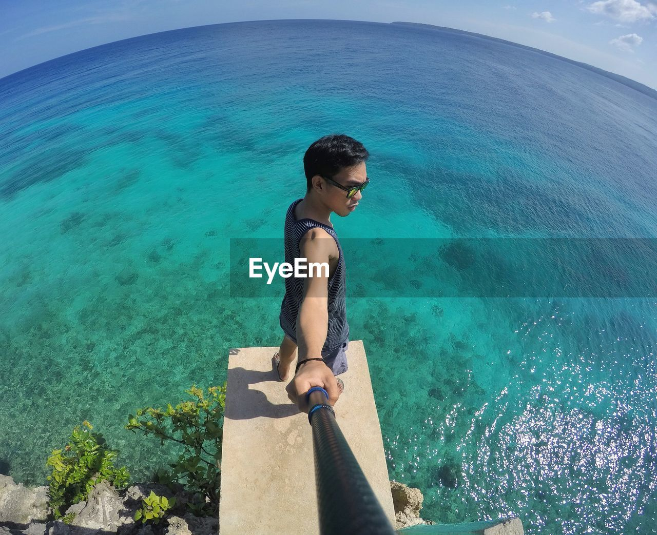 Fish-eye lens of young man with monopod standing on pier over sea