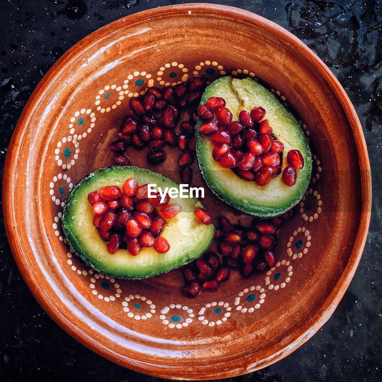 High angle view of pomegranate with avocado in bowl on slate