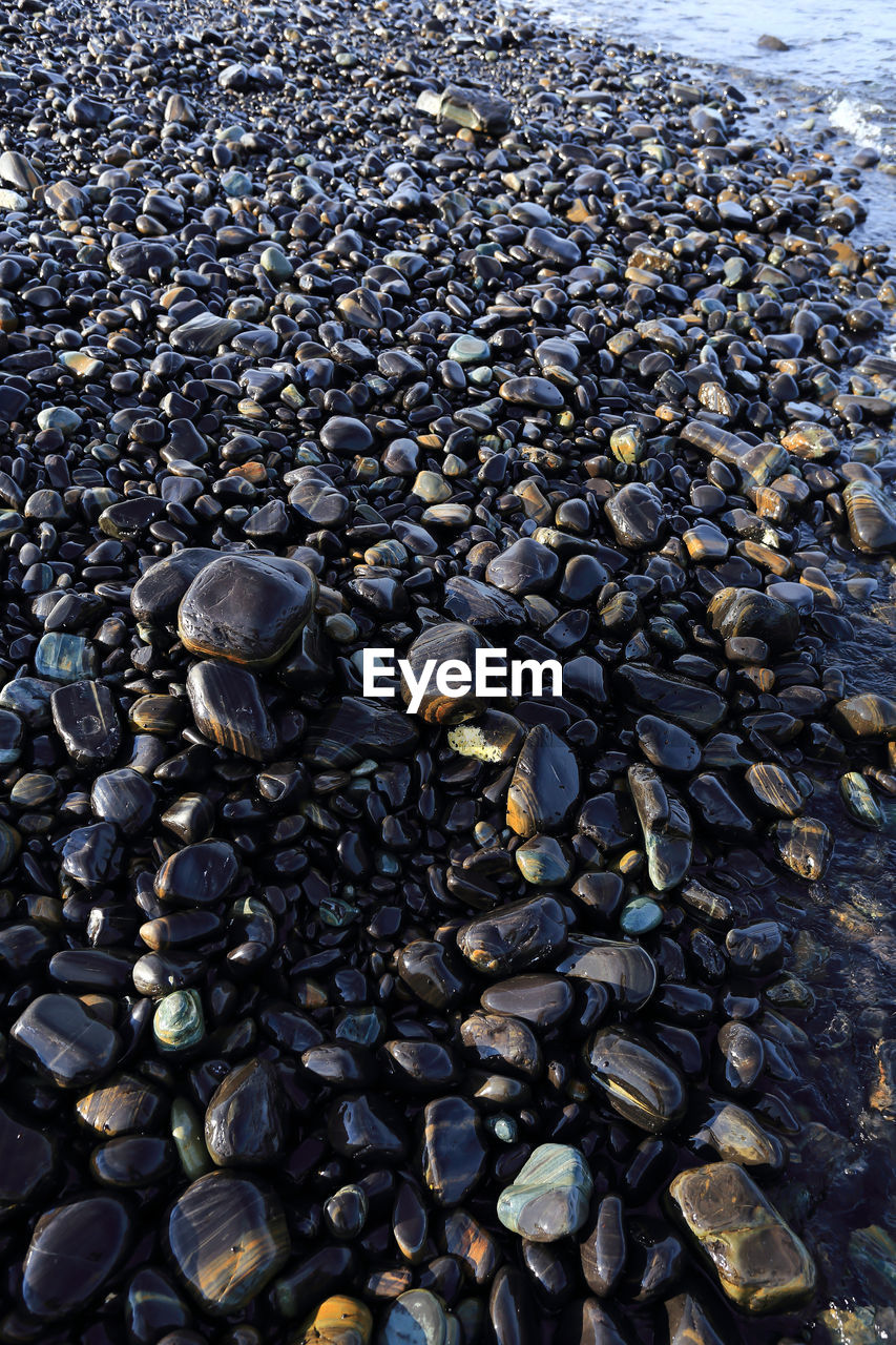 abundance, large group of objects, no people, full frame, nature, high angle view, pebble, backgrounds, day, stone - object, beach, land, stone, sunlight, rock, close-up, solid, still life, tranquility, outdoors, caffeine, marine