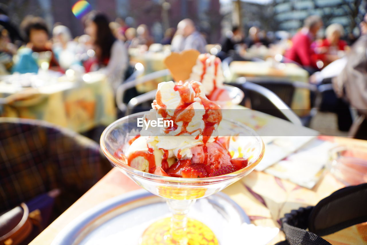 food and drink, food, incidental people, freshness, focus on foreground, ready-to-eat, restaurant, business, table, indulgence, close-up, serving size, dessert, sweet food, sweet, real people, group of people, ice cream, temptation, day, glass