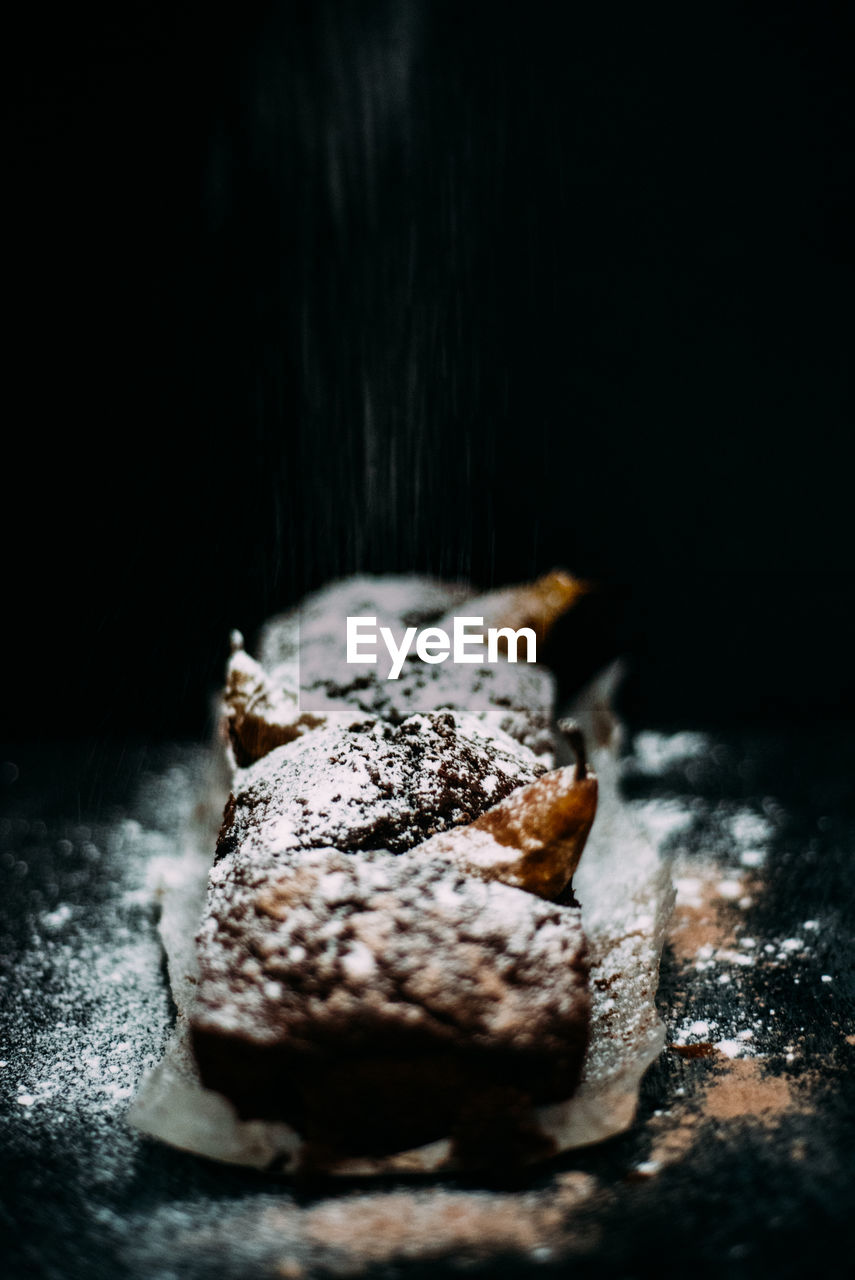 Close-up of dessert with powdered sugar against black background