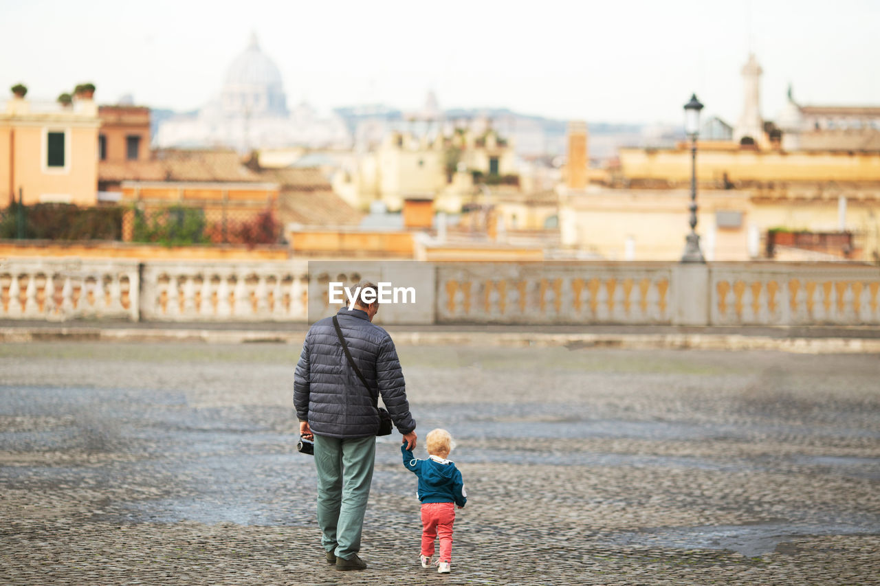 Rear view of grandfather holding granddaughter hand while walking on road